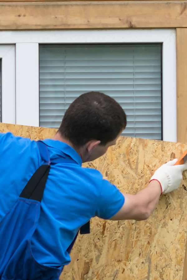 a man obstructs a window with a large piece of plywood before a natural disaster, a hurricane